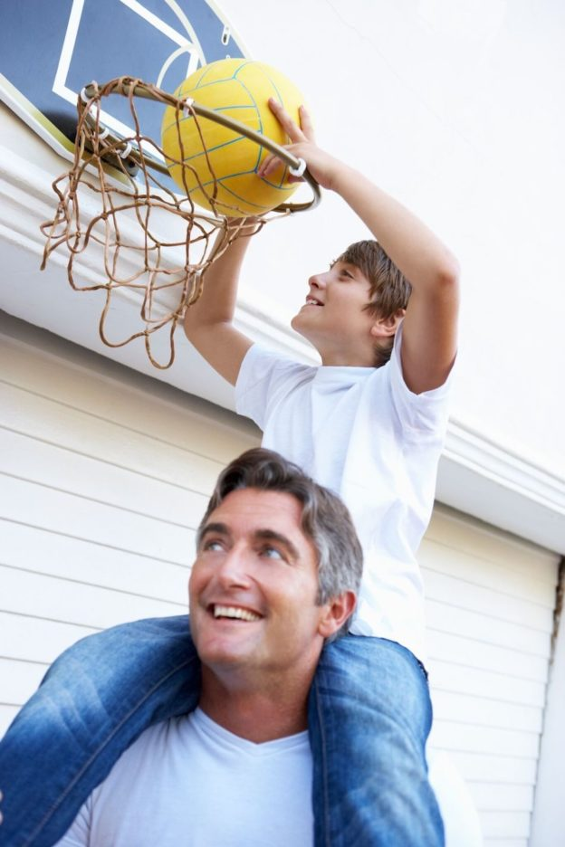 Father and Son Playing Basketball in front of Creative Door Garage