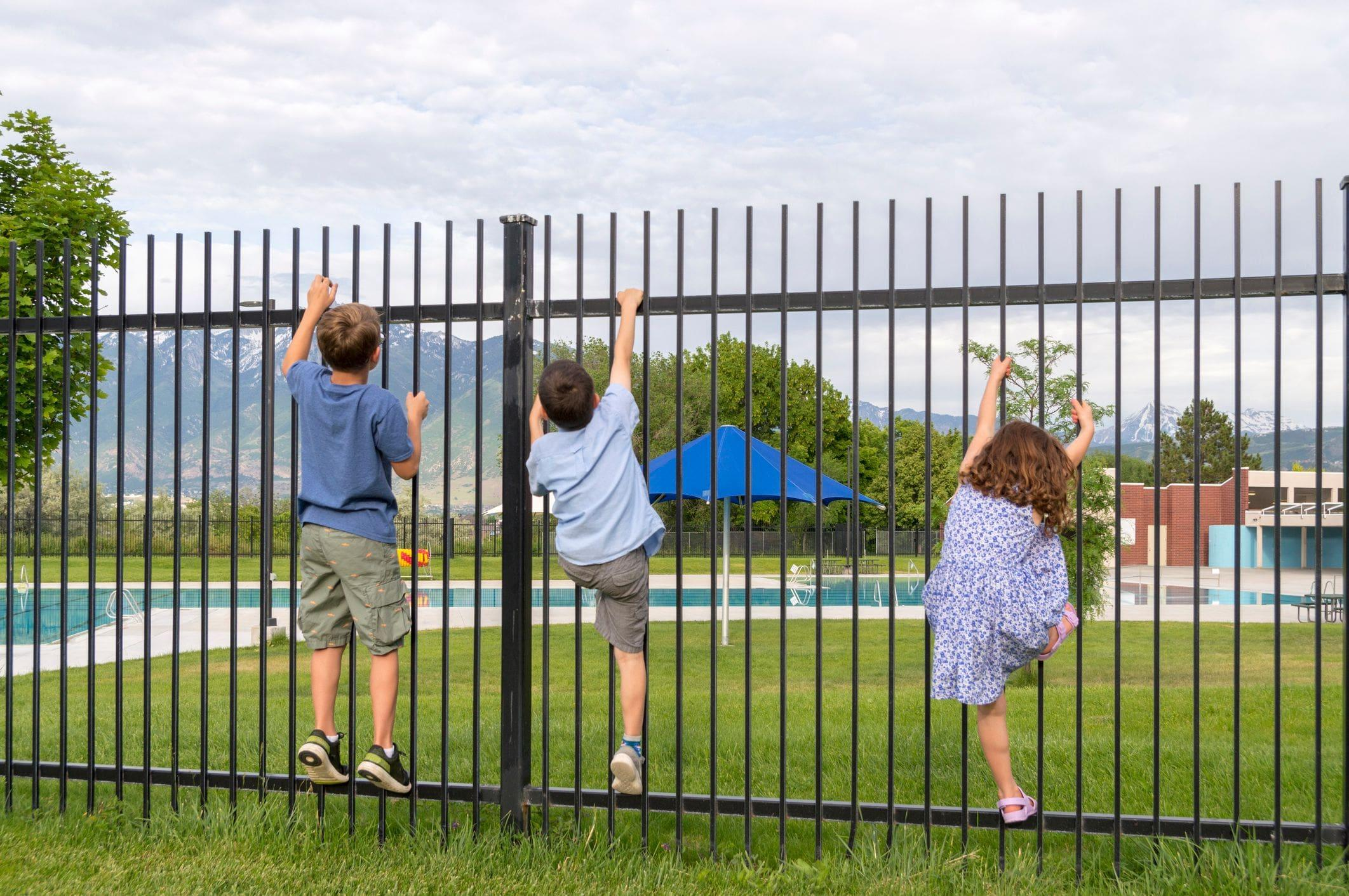 children trying to climb a gate to get to a restricted pool area