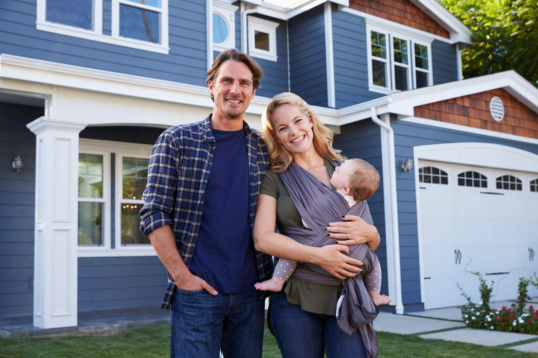 couple holding baby in front of new home