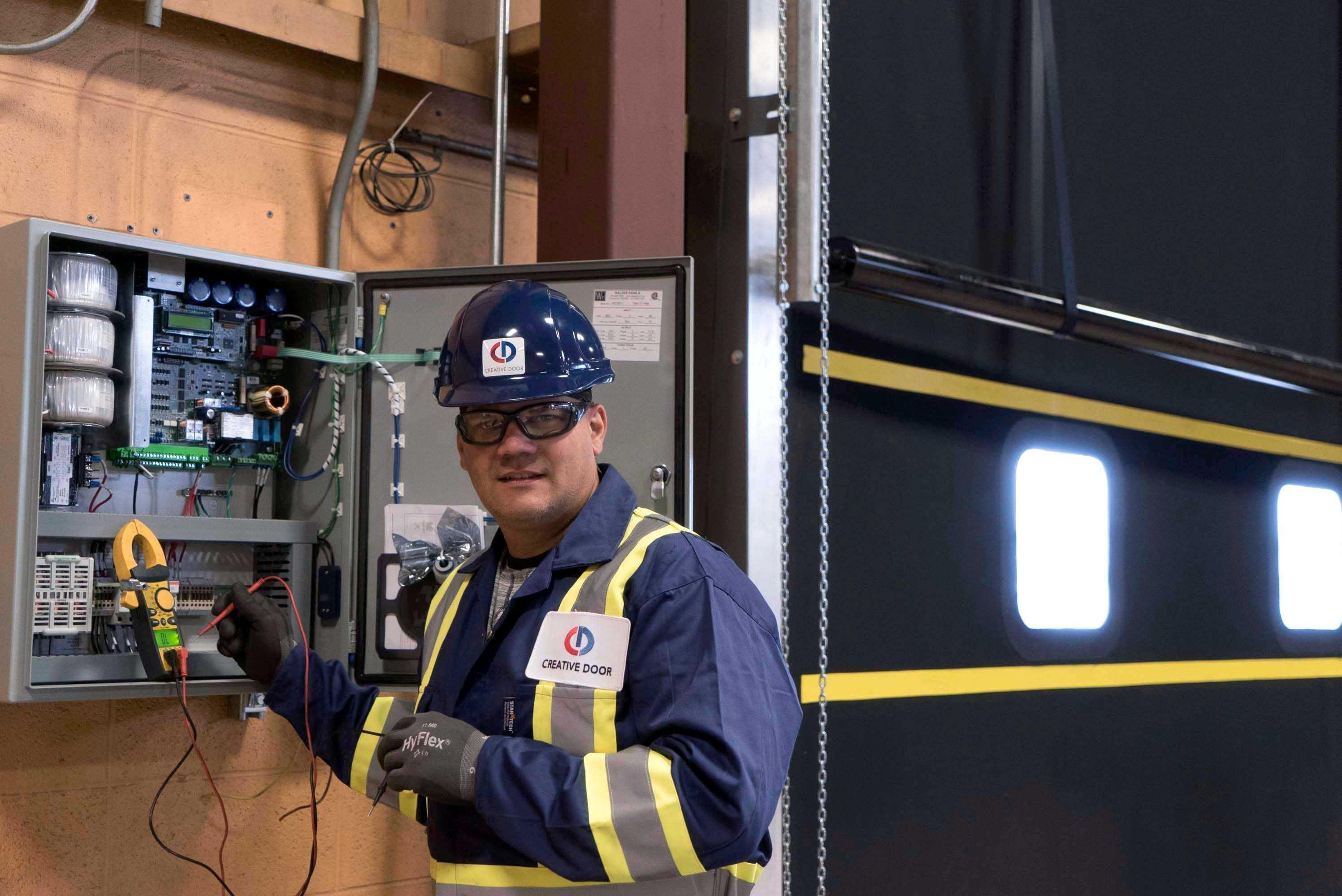 creative door technician working on electrical panel for overhead door operation