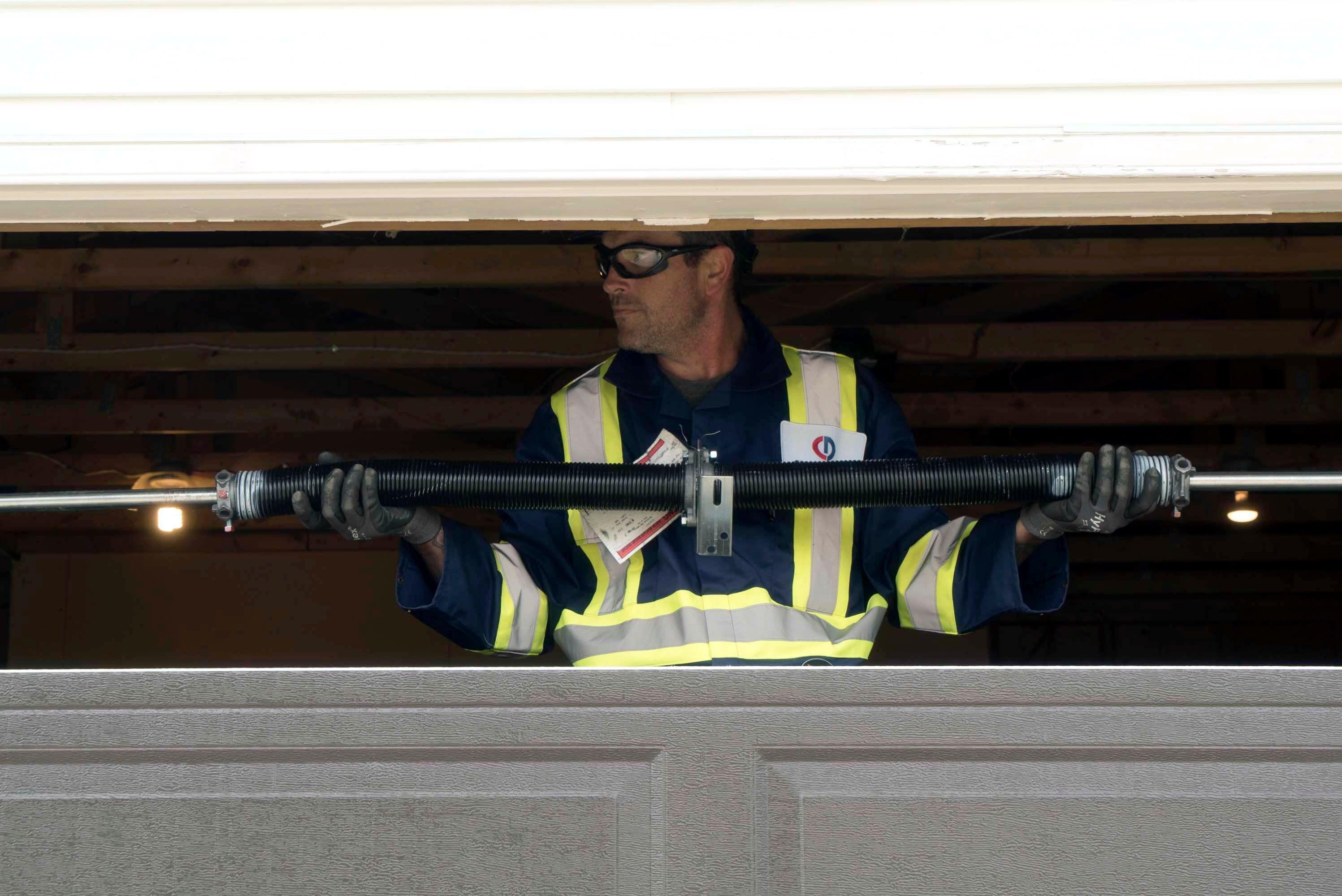 technician holding garage door springs