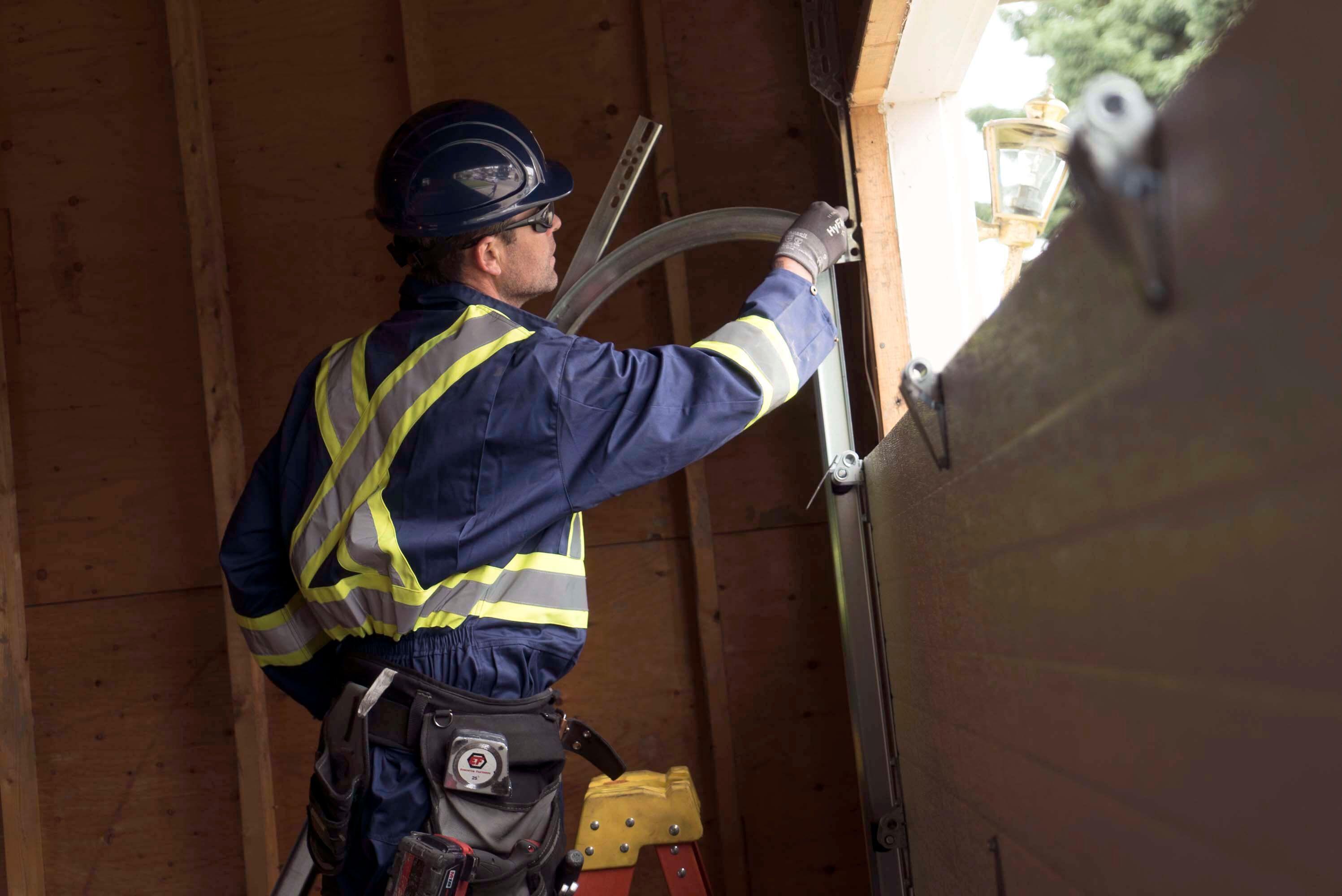 technician inspecting garage door tracks