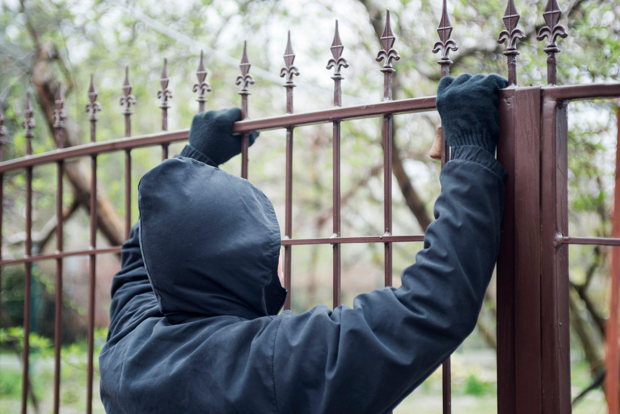 intruder wearing dark gloves and hoodie peers over ornamental wrought iron gate