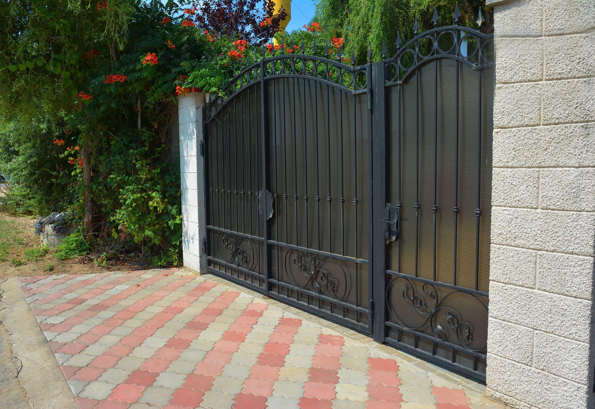 black ornamental gate with vibrant green and red plants