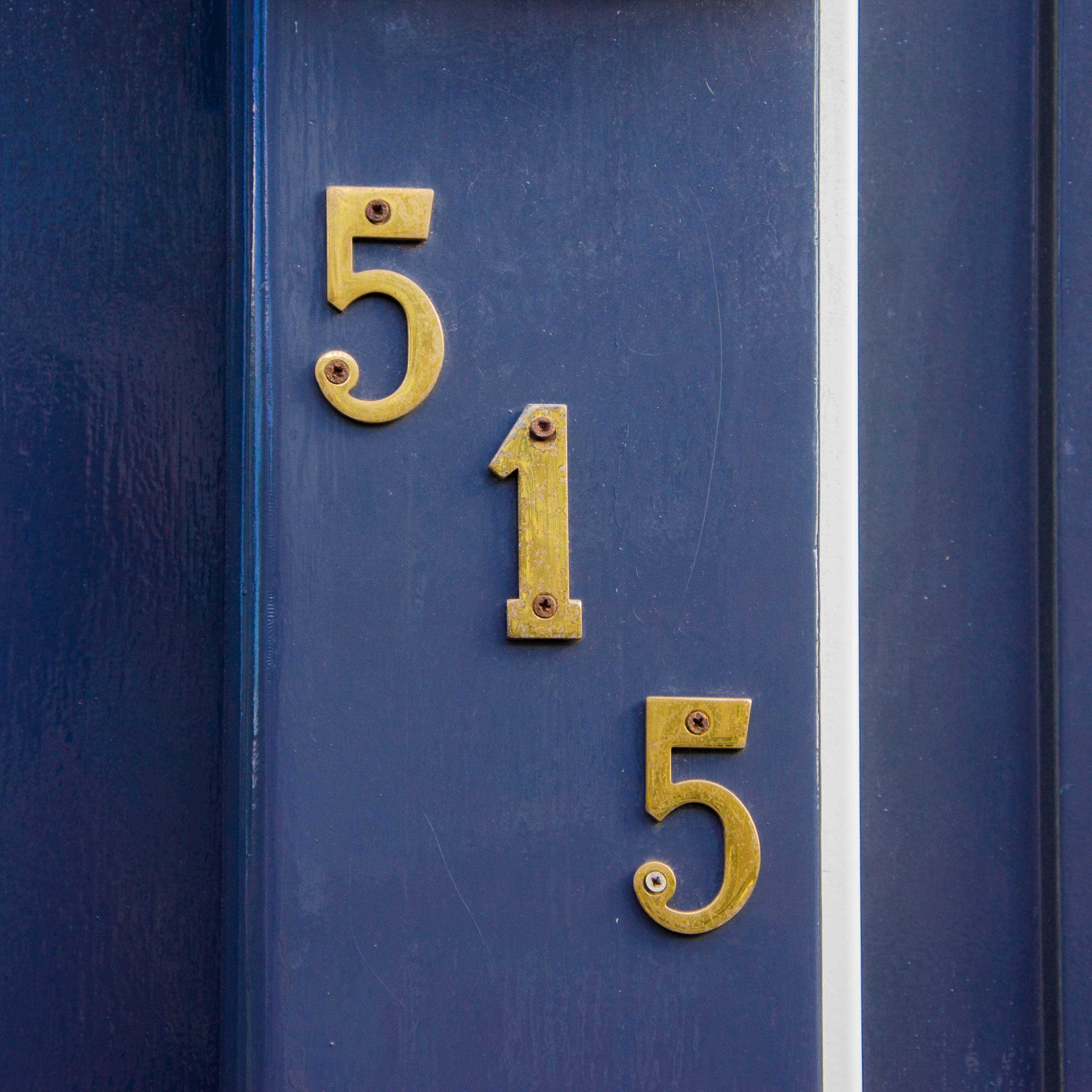 house number displayed on navy blue door trim