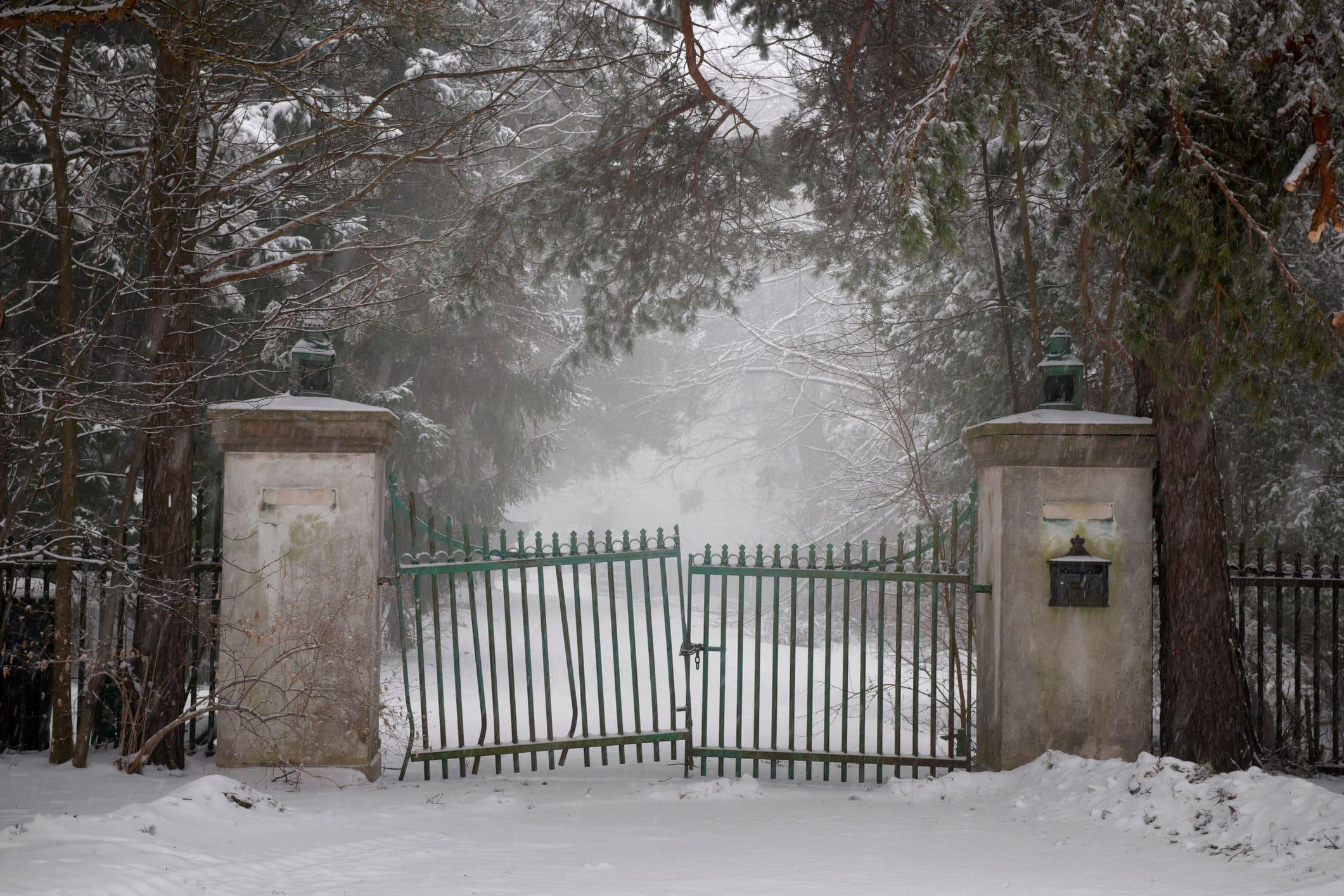 snowy driveway with a neglected run down gate