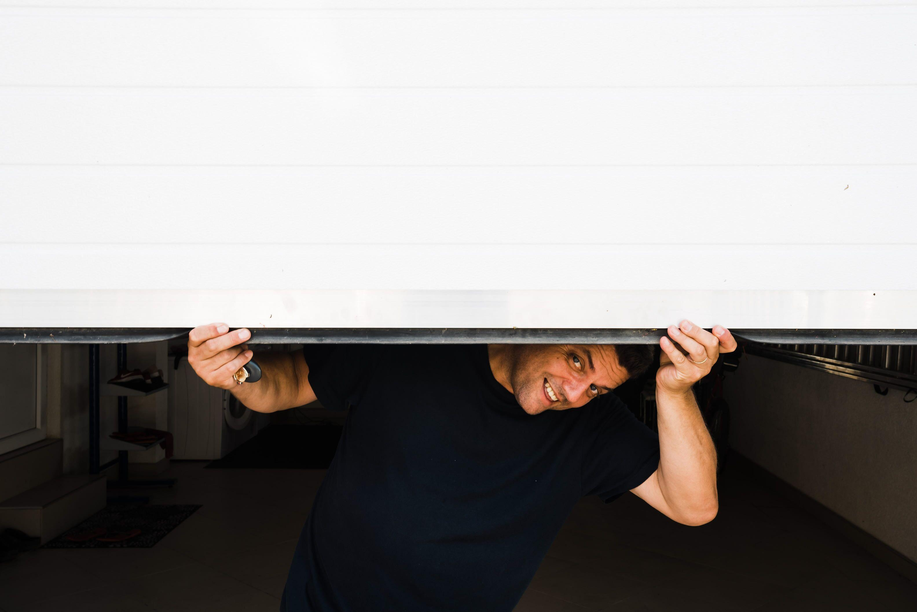 a man peaking out from his half-open and stuck garage door