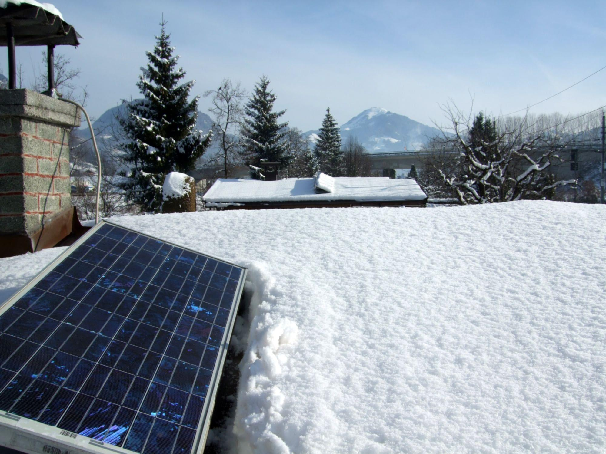 solar panel on snowy residential roof with mountains in background