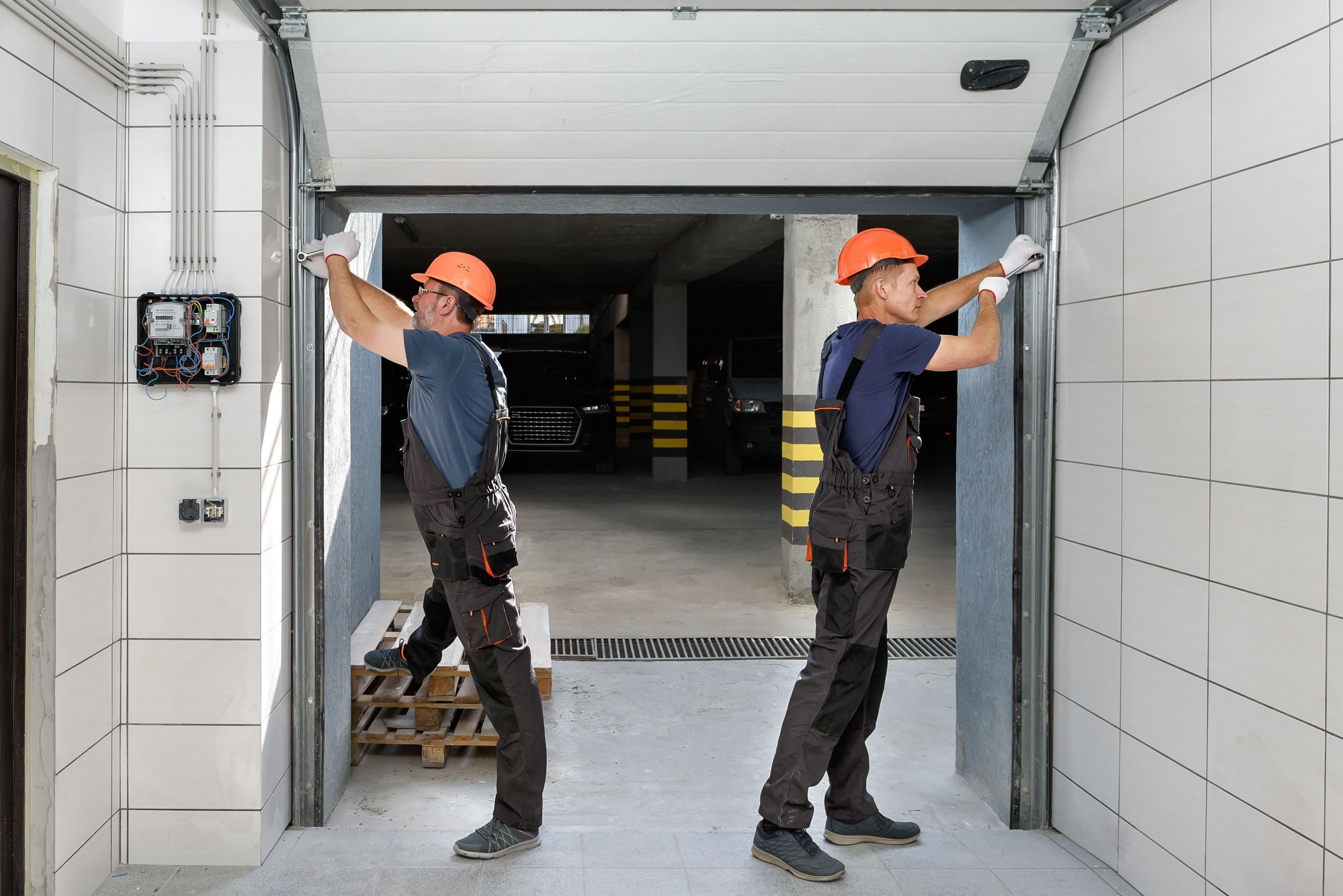 two technicians replacing garage door rollers in a parking garage