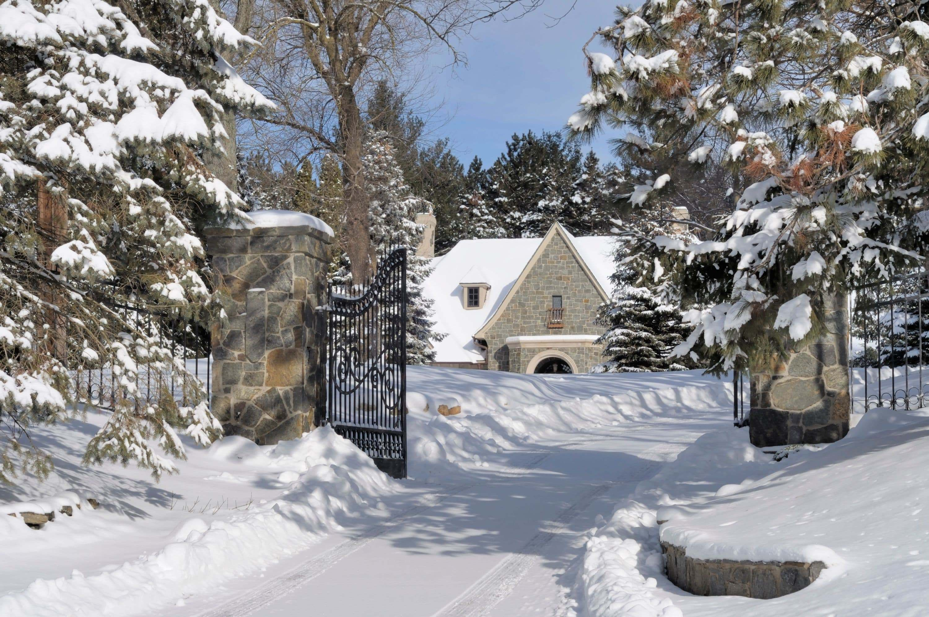 beautiful stone and steel gate with fresh snowfall around winter estate