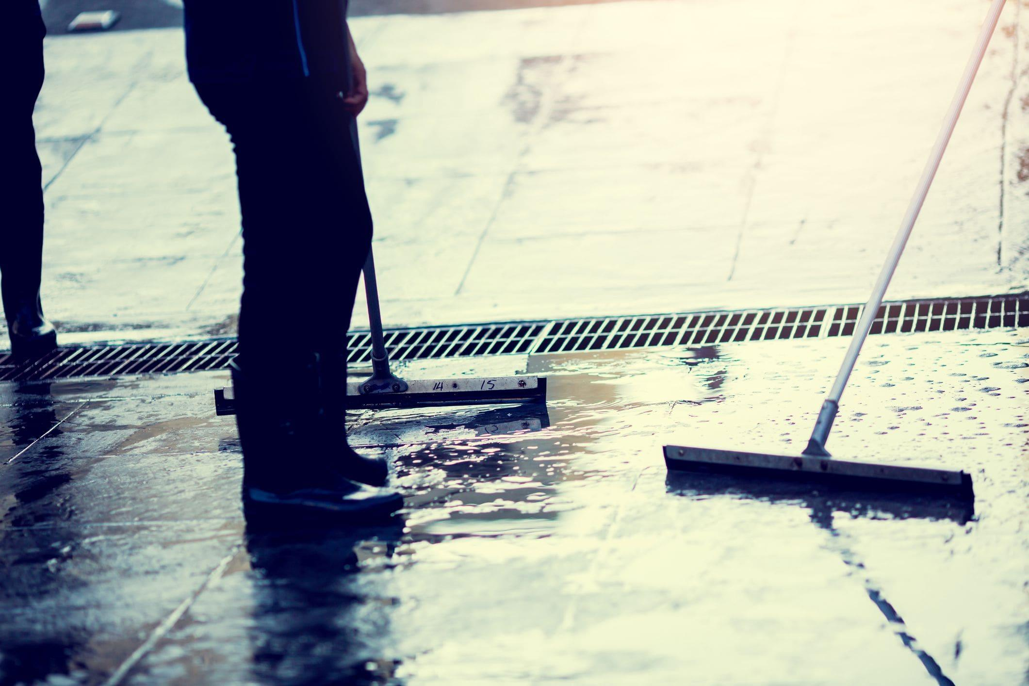 using a floor squeegee to sweep out water from garage