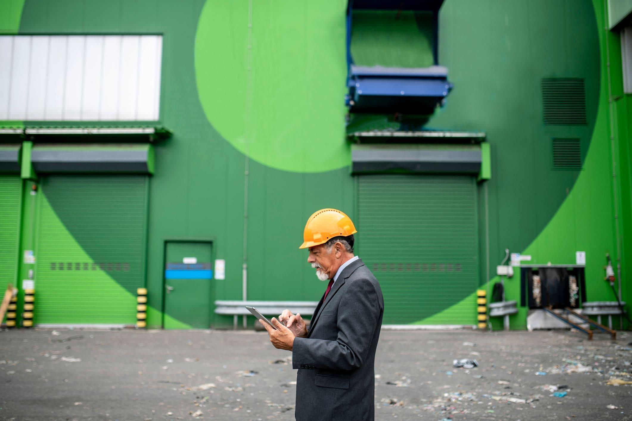 site manager outside colourful green warehouse with pedestrian doors